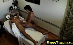 Busty asian masseuse tugging a client