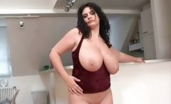 Chubby, busty brunette poses and plays with her pussy in kitchen